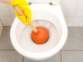 personnage avec un gant jaune en train de déboucher des wc à l'aide d'une ventouse