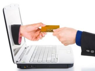 Main qui tend une carte bancaire à travers un écran