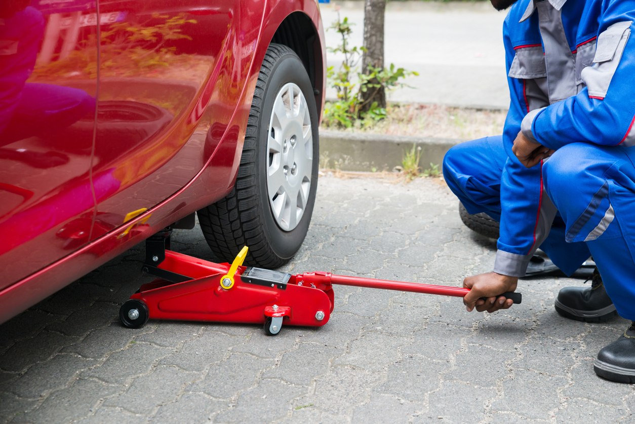 Un mécanicien avec un cric sous une voiture